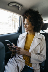 Smiling woman sitting in back seat of a car holding cell phone - JRFF02803