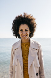Portrait of smiling woman with the sea in background - JRFF02812