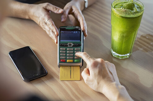 Cropped hands of female customer making credit card payment to owner on wooden table in cafeteria - CAVF62104