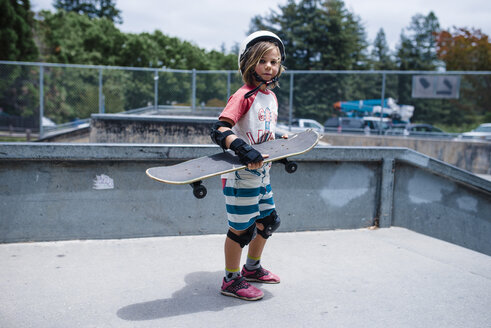 Portrait of girl holding skateboard while standing on sports ramp at park - CAVF62119