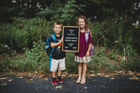 Full length portrait of smiling siblings with backpack and blackboard standing on road - CAVF62137