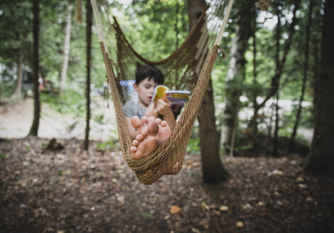 Full length of boy reading book while relaxing on hammock in forest - CAVF62152