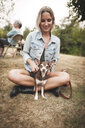 Smiling woman playing with Chihuahua while sitting on grassy field in yard - CAVF62179