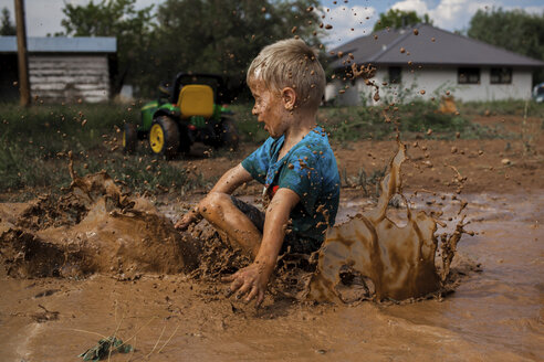 Side view of playful boy sitting on muddy puddle in yard - CAVF62206