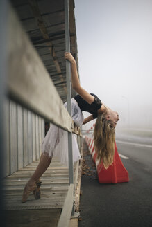 Side view of ballerina stretching at sidewalk in city - CAVF62209