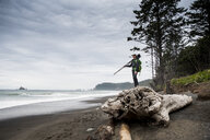 Side view of male hiker with tripod standing on log at beach against cloudy sky in Olympic National Park - CAVF62215