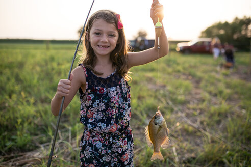 Portrait of smiling girl holding dead fish in fishing line on field during sunset - CAVF62218