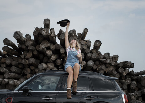 Happy woman holding hat while sitting on car roof against logs at Algonquin Provincial Park - CAVF62290