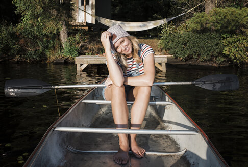Portrait of smiling woman sitting in boat on lake at Algonquin Provincial Park - CAVF62293