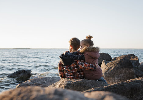 Rear view of siblings sitting on rocks at lakeshore against clear sky during sunset - CAVF62305