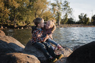 Happy siblings sitting on rock by Lake Simcoe during sunset - CAVF62311