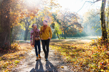 Couple walking in autumnal park, Strandbad, Mannheim, Germany - CUF49273