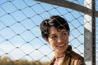 Smiling woman behind fence - CUF49282