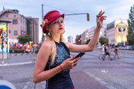 Hipster woman hailing cab, Berlin, Germany - CUF49297