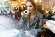 Young woman drinking coffee with friend in cafe, London, UK - CUF49363