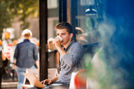 Young man drinking coffee and using laptop at cafe - CUF49366