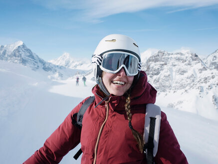 Young woman skier wearing helmet and ski goggles smiling in snow covered landscape,  portrait, Alpe Ciamporino, Piemonte, Italy - CUF49411