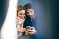 Couple using smartphone inside train - CUF49447