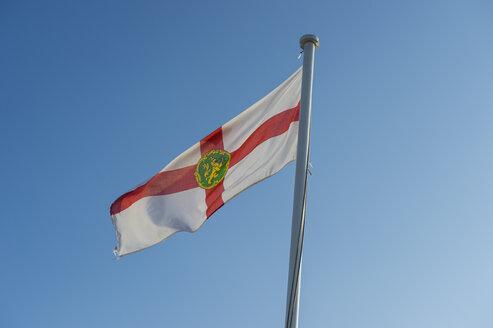 United Kingdom, Channel Islands, Alderney, Flag of Alderney against blue sky - RUNF01465
