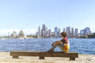 Australia, New South Wales, Sydney, man looking at Sydney Skyline with Opera and Financial District - KIJF02342
