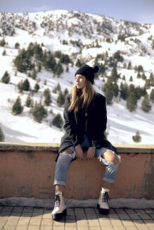 Spain, Benasque, portrait of young woman sitting on a wall in winter - ACPF00473