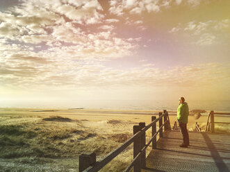 Belgium, Flanders, North Sea, Coast, sunset light, man standing on boardwalk in sand dunes, relaxing, watching ocean and listening to ocean sounds - GWF05914