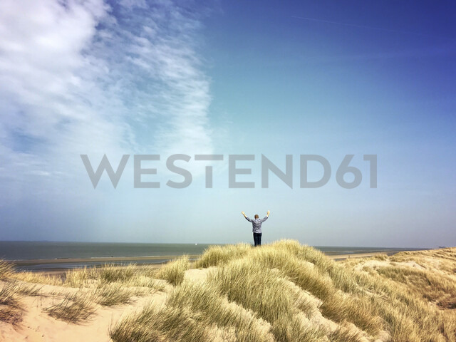 Belgium, Flanders, North Sea, Coast, man relaxing in sand dunes, doing exercise and watching ocean, listening to ocean sounds in warm spring sunshine - GWF05923 - Gaby Wojciech/Westend61
