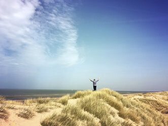 Belgium, Flanders, North Sea, Coast, man relaxing in sand dunes, doing exercise and watching ocean, listening to ocean sounds in warm spring sunshine - GWF05923