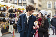 Happy young couple strolling at Christmas market - MGIF00302
