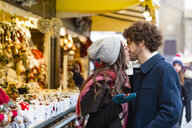 Happy affectionate young couple kissing at Christmas market - MGIF00305