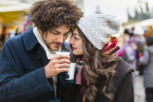 Happy affectionate young couple with hot drinks at Christmas market - MGIF00308