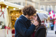 Affectionate young couple kissing at Christmas market - MGIF00311