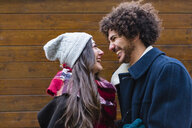 Happy young couple in winterwear in front of wooden wall - MGIF00317