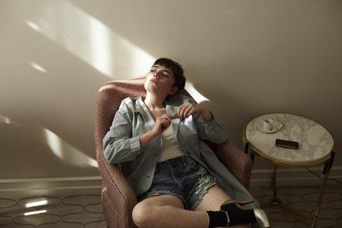 Teenage girl sitting in armchair looking away - AMEF00024