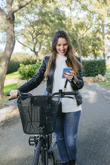 Smiling young woman with bicycle in park using cell phone - KIJF02364
