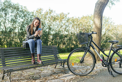 Young woman with bicycle sitting on a bench in park using cell phone - KIJF02367