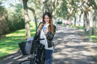 Smiling young woman with bicycle in park using cell phone - KIJF02373