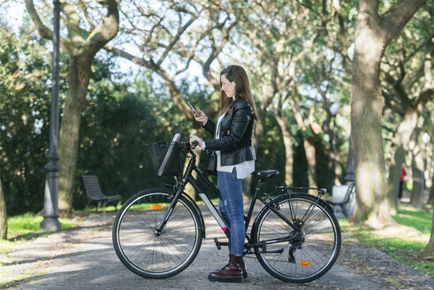Young woman with bicycle in park using cell phone - KIJF02379
