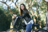 Portrait of smiling young woman with bicycle and cell phone in park - KIJF02382