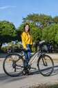 Portrait of smiling young woman with bicycle and headphones in park - KIJF02385