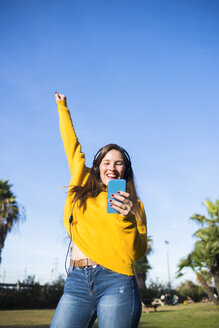 Happy young woman with cell phone listening to music with headphones - KIJF02388