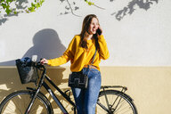 Young woman with bicycle talking on cell phone at a wall - KIJF02391