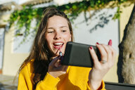 Young woman applying lipstick looking at herself on the cell phone - KIJF02394