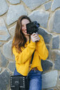 Young woman with vintage camera at a stone wall - KIJF02397