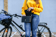 Close-up of woman with bicycle looking in handbag - KIJF02400