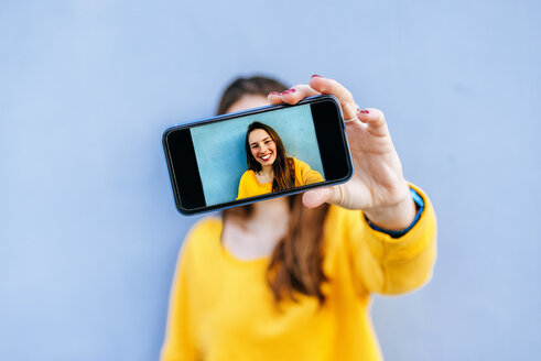 Smiling young woman taking a selfie at a blue wall - KIJF02403