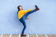 Playful young woman with raised leg at blue wall - KIJF02406