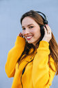 Portrait of smiling young woman listening to music with headphones - KIJF02409