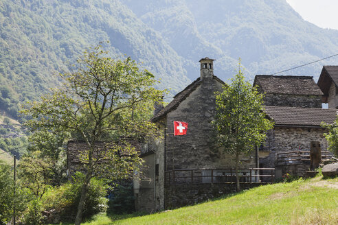 Switzerland, Ticino, Verzasca Valley, typical stone house with Swiss National Flag - GWF05948