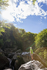 Switzerland, Ticino, Verzasca Valley, man standing on rock looking at waterfall - GWF05960